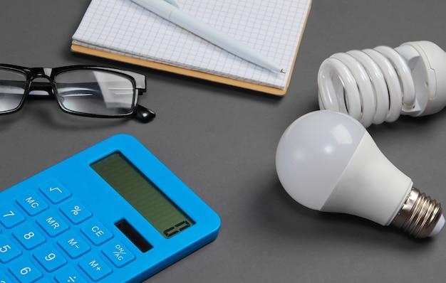 에너지 절약 분석. 전구, 회색에 노트북 계산기.