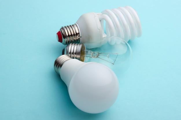 Энергосберегающие и лампы накаливания крупным планом на синем пастельном фоне