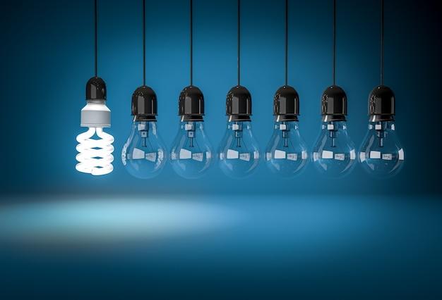 青い背景上のワイヤーに白熱電球を照明する省エネ電球。イノベーションのコンセプト。