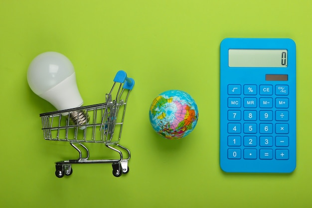 Energy saving. calculator, shopping trolley with led light bulb and globe on green background. save planet. eco concept. top view