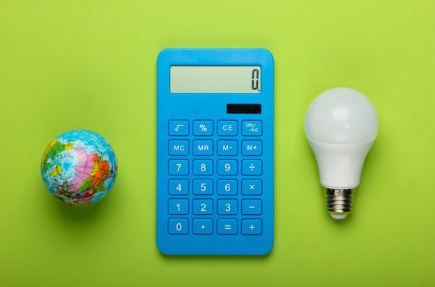 Energy saving. calculator with led light bulb and globe on green background. save planet. eco concept. top view
