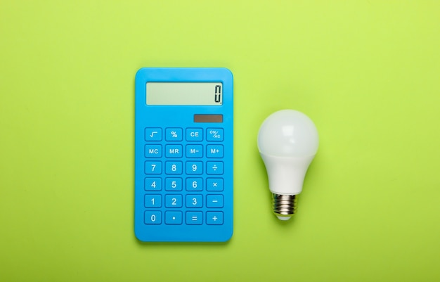 Energy saving. calculator with led light bulb on green background. top view