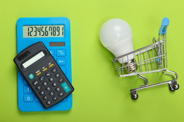 Energy saving. calculators and shopping trolley with led light bulb on green background. top view