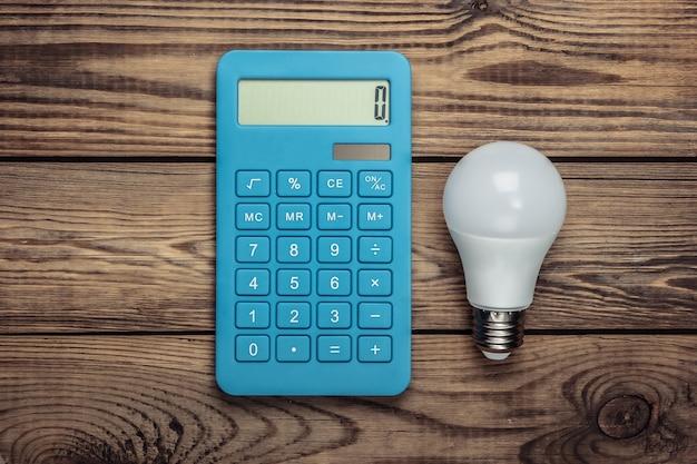 Концепция энергосбережения. калькулятор с лампочкой на деревянном