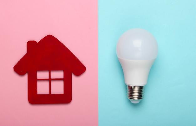 에너지 절약 개념. 블루 핑크 파스텔 배경에 집 입상 및 에너지 절약 전구. 평면도