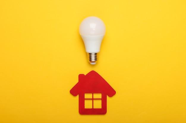 에너지 절약 개념. 노란색 바탕에 집 입상 및 에너지 절약 전구. 평면도
