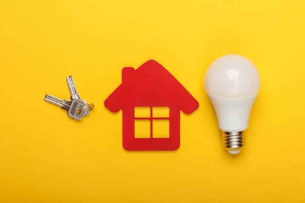 에너지 절약 개념. 키와 노란색 배경에 에너지 절약 전구 집 입상. 평면도