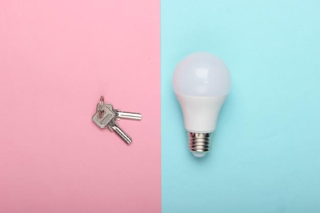 에너지 절약 개념. 블루 핑크 파스텔 배경에 키와 에너지 절약 전구. 평면도