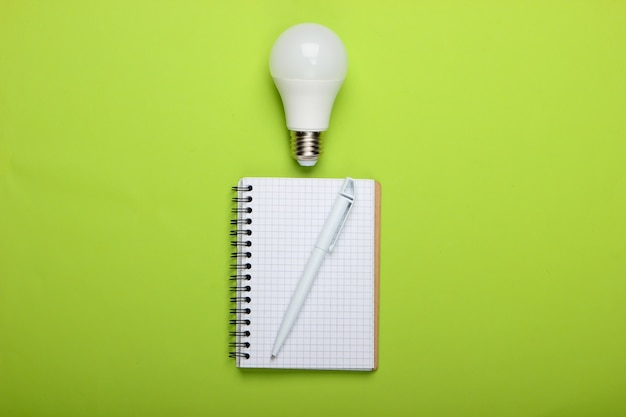 Energy saving concept. notepad with led light bulb on a green background. i have an idea!