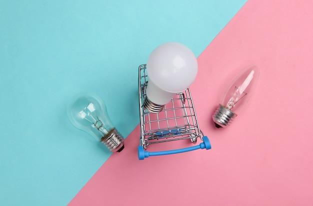 에너지 절약 개념. 핑크 블루 파스텔에 슈퍼마켓 쇼핑 트롤리와 전구