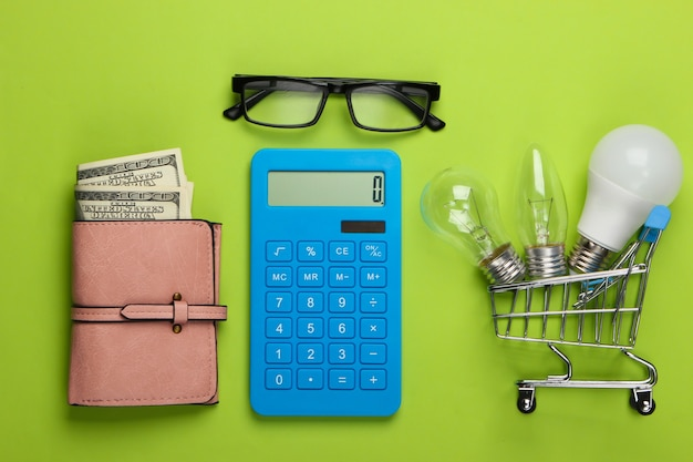 Energy saving concept. supermarket shopping trolley and light bulbs, calculator and purse on green