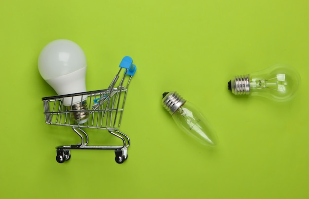 Energy saving concept. supermarket shopping trolley and light bulbs on green