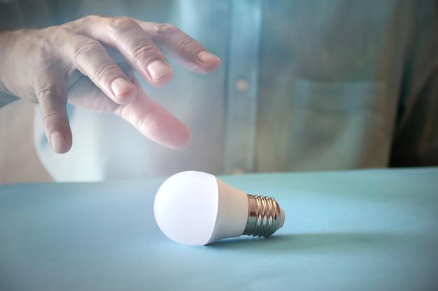 電球と手で省エネコンセプト。スペースをコピーします。セレクティブフォーカス。