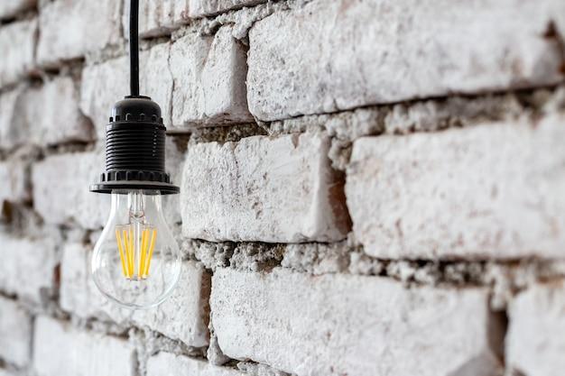 Энергосберегающая светодиодная лампа, висящая на грубой белой стене в роскошном дизайне современного гостиничного номера в стиле лофт.