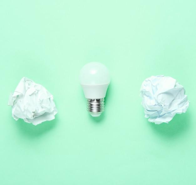 Энергосберегающие светодиодные лампочки и скомканные бумажные шарики на зеленом фоне. минималистичная бизнес-концепция, идея. вид сверху