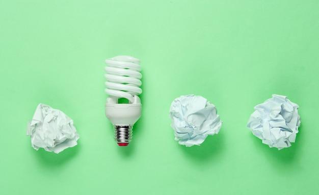 Энергосберегающая электрическая лампочка и скомканные бумажные шарики на зеленом фоне. минималистичная бизнес-концепция, идея. вид сверху
