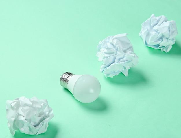 Энергосберегающая электрическая лампочка и скомканные бумажные шарики на зеленом фоне. минималистичная бизнес-концепция, идея.