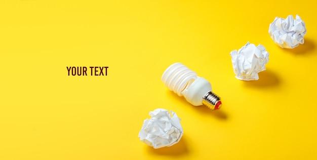 에너지 절약 전구 및 노란색 바탕에 구겨진 된 종이 공. 최소한의 비즈니스 개념, 아이디어. 공간 복사