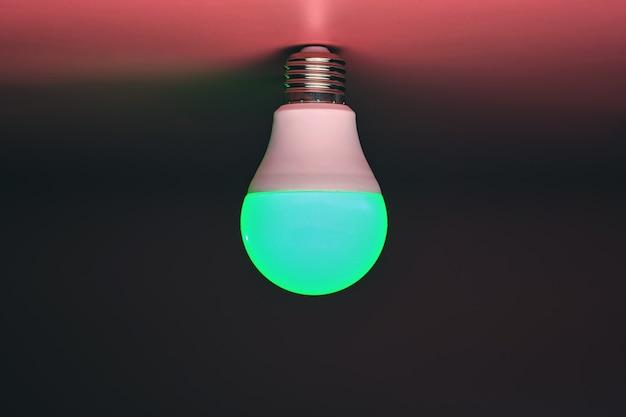 에너지 절약 전구, 빛나는 녹색 빛, 복사 공간. 최소한의 아이디어 개념.