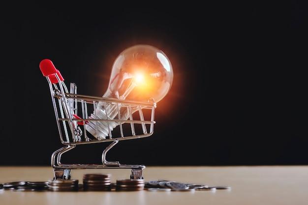 Идея энергосберегающей лампочки с тележкой для покупок и финансовой концепцией