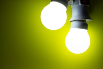 Energy saving light bulb on yellow background
