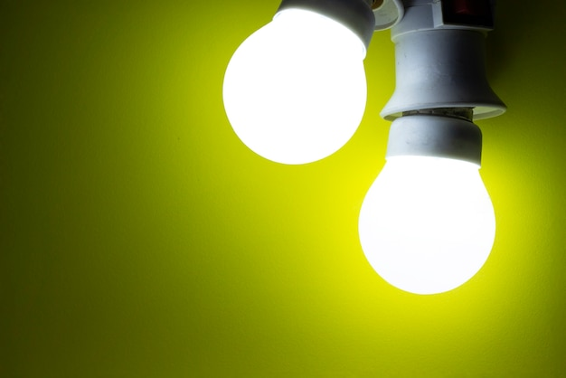 Energy saving light bulb on yellow background