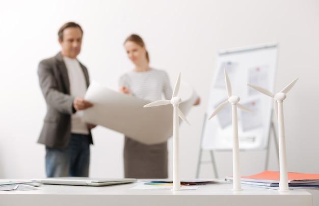 에너지 절약. 전문 동료 엔지니어가 에코 프로젝트를 논의하고 청사진을 들고있는 동안 테이블에 서있는 풍력 터빈의 선택적 초점