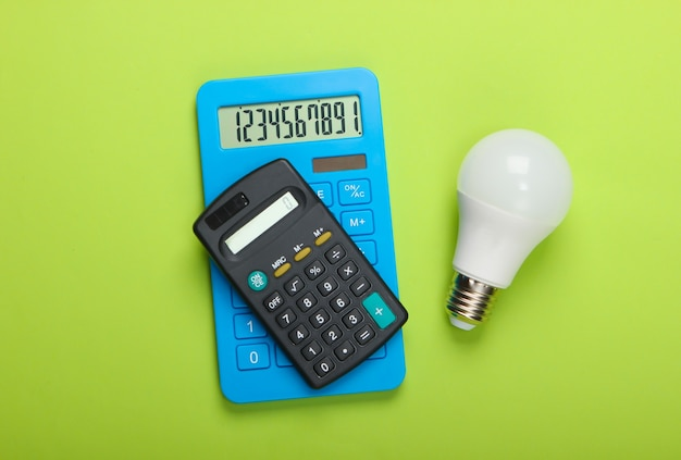 Energy saving. two calculators with led light bulb on green background. top view