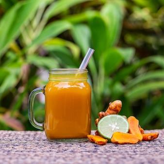Энергетический тонизирующий напиток с куркумой, имбирем, лимоном и медом в стеклянной кружке, фоне природы, крупным планом