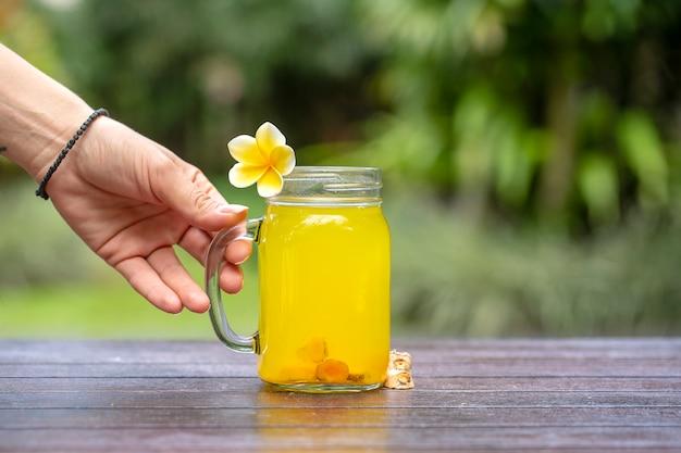 Энергетический тонизирующий напиток с куркумой, имбирем, лимоном и медом в стеклянной кружке