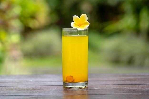 Энергетический тонизирующий напиток с куркумой, имбирем, лимоном и медом в стакане