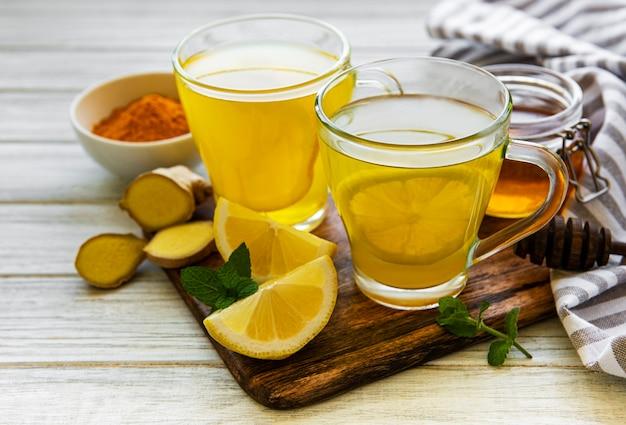 白い大理石の表面にターメリック、ジンジャー、レモン、蜂蜜を使ったエネルギートニックドリンク