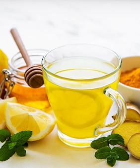 Энергетический тонизирующий напиток с куркумой, имбирем, лимоном и медом на белом мраморе