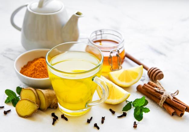 Энергетический тонизирующий напиток с куркумой, имбирем, лимоном и медом на белом деревянном фоне