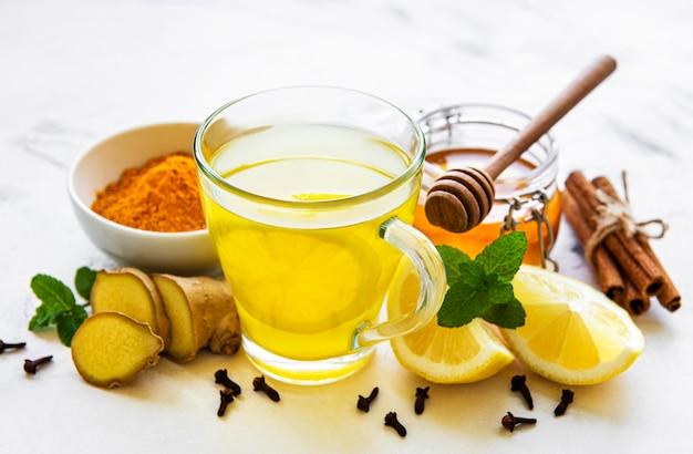 Энергетический тонизирующий напиток с куркумой, имбирем, лимоном и медом на белом деревянном