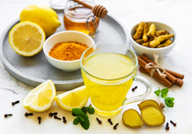 Energy tonic drink with turmeric, ginger, lemon and honey on a white marble background