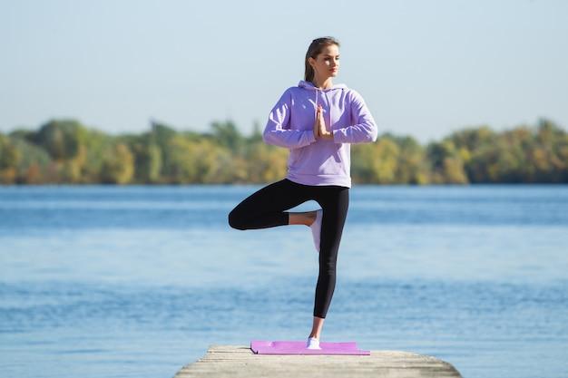 エネルギー。若い女性アスリート、女性のトレーニング、秋の日差しの中で屋外で練習
