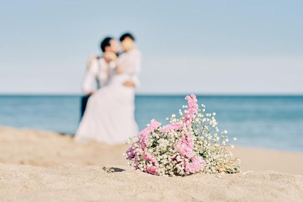 해변에서 키스하는 약혼 된 커플