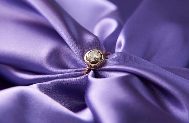 Обручальное кольцо с бриллиантом на зеленом атласном фоне. золотое кольцо с бриллиантом, крупный план. роскошные женские украшения, крупный план. селективный фокус