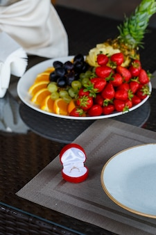 果物の背景に赤いボックスの女の子のための婚約金の貴重なジュエリーリング