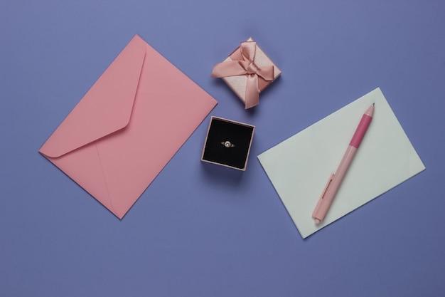 ギフトボックスにダイヤモンドの婚約ゴールドリング、紫色の背景に結婚式の招待状の封筒。上面図。フラットレイ