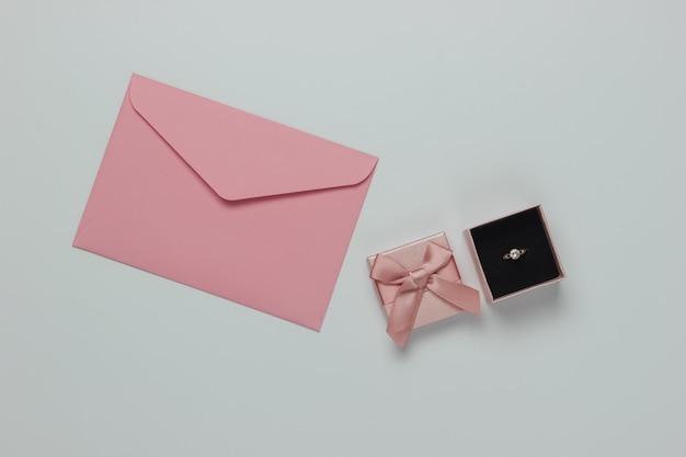 ギフトボックスにダイヤモンドの婚約ゴールドリング、白い背景に結婚式の招待状の封筒。上面図。フラットレイ