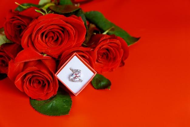 Обручальное кольцо и красивая красная роза на красном фоне. день святого валентина.