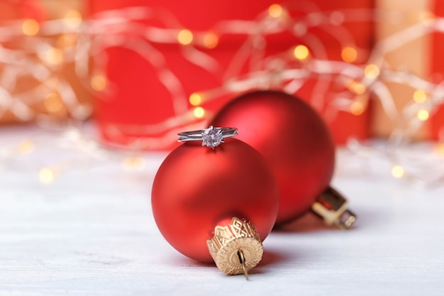 Обручальное кольцо и елочные шары на столе, крупным планом