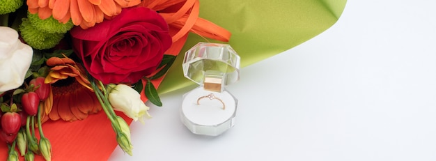 Engagement ring in a gift box with bright bouquet of flowers. the offer to get married. gift for st. valentine's day. marriage proposal for beloved woman. symbol of love and marriage.