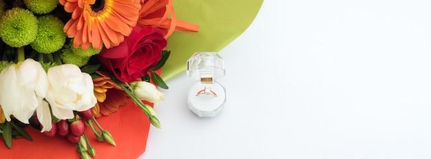 明るい花束とギフトボックスの婚約指輪。結婚の申し出。聖バレンタインの日のためのギフト。最愛の女性のための結婚提案。愛と結婚の象徴。