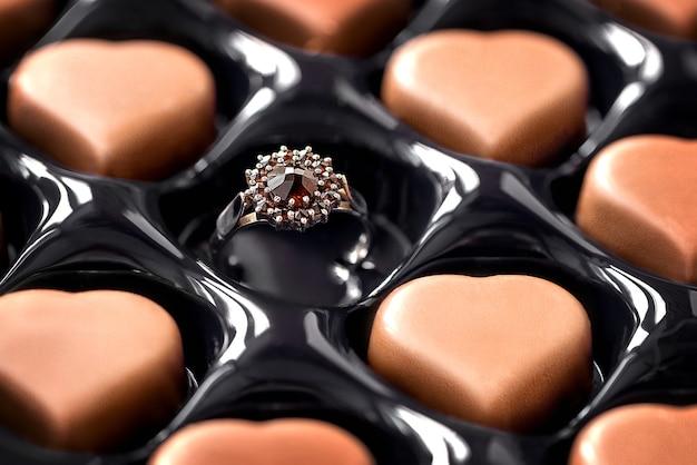ハート型のチョコレートが入った箱の空のセルにある婚約指輪。バレンタインデーのお祝いの贈り物