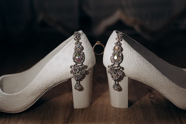 Engagement ring is located between bride's decorated heels