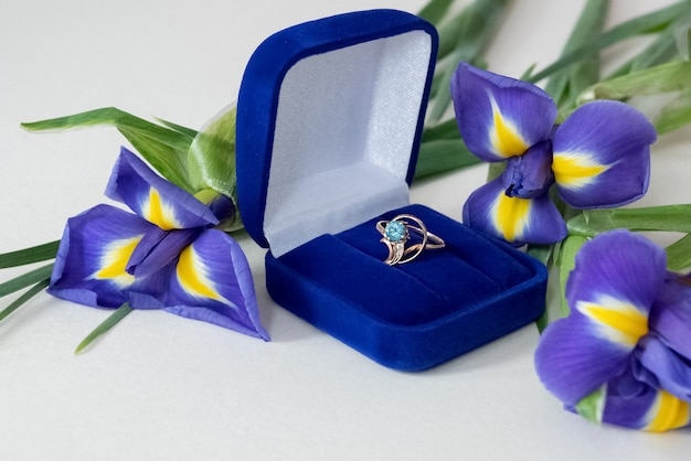 Engagement ring made of gold with blue topaz precious gem in jewelry box and bouquet of blooming irises scattered around