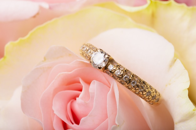 Engagement ring on natural romantic pink flower